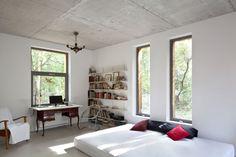W wystroju tej sypialni minimalistyczne elementy – wysoki materac w charakterze łóżka, chromowane krzesło i prosty regał efektownie zestawiono ze stylowym biurkiem, żyrandolem i lampą biurową. Dzięki takiemu eklektyzmowi wnętrze wykończone surowym betonem i szarą żywicą wydaje się przytulniejsze i ma charakter. Nieosłonięte wielkie okna wpuszczają do środka światło i zdobią pokój widokiem na las.