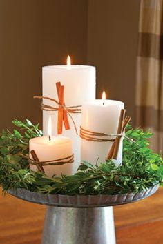 Wrap pillar candles with jute, and tuck in cinnamon sticks. Place in a ring of greenery on top of a cake pedestal.