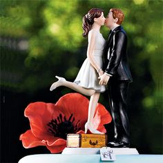 "This ""A Kiss and We're Off"" cake topper couple shows all the excitement of a bride and groom about to start off on their first journey together as husband and wife. While perched on a suitcase with a tag that says ""Honeymoon Bound"" the Bride steals a precious moment to kiss her Groom."