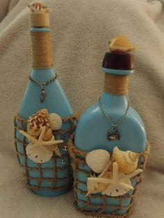 Bottles are upcycled Bottega Italian measuring 13t x 5w x 1 3/4 d. Eligah Craig bottle measuring 11 3/4 t x 5w x 4d. Both are painted aqua and decorated with jute, shells, and charms. These bottles can be used for a centerpiece, accent decor, or a vase.