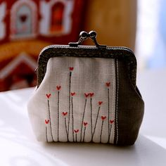 Grey linen and Red hearts little coin Purse.This little purse is designed and hand sewed by me. It is made from beautiful linen fabrics with hand stiched hearts. The whole clutch is lined with cotton fabrics. A layer of cotton is padded in between for added softness.  No glue used. Sewed on the metal frame for durability.