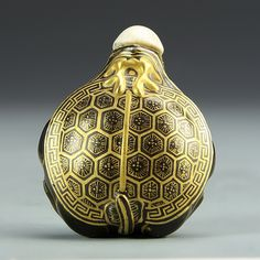 China, 19th C., gilt porcelain snuff bottle, compressed circular form with stylized turtle painted in gilt, gilted key fret surrounded turtle shell with Qianlong mark, stopper emerges from turtle figure's mouth. Height 2 1/4 in.