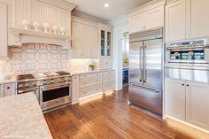 A patterned backsplash and hardwood floor accent this neutral kitchen. The Rangemoss, plan 1211. http://www.dongardner.com/house-plan/1211/the-rangemoss. #Kitchen #Design #FloorPlan