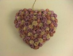 Folded Rose Tutorial  Polly Wiggins, a quilling friend in Kansas, encrusted this paper mache heart with beautiful folded roses and fringed flowers. I'm drawn to the subtle, old fashioned shades she chose, perhaps because they remind me of a silky-soft comforter my great grandmother made years and years ago.
