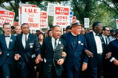 Leaders of the March on Washington for Jobs and Freedom march with signs (from R-L): Matthew Ahmann, Floyd McKissick, Martin Luther King Jr., Rev. Eugene Carson Blake and unidentified.
