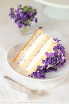 Close-up slice of violet cake with violet jam and fresh edible violet decorations