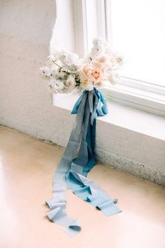 Modern ombre bridal bouquet by Helmivillakko in white to soft peach with heaps of beautiful blue silk ribbons by Seidenband! Captured by Petra Veikkola Photography in her light filled contemporary wedding inspiration shoot at Laukon Kartano in Finland - featured on B.LOVED Blog