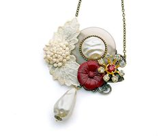 Mixed media necklace in ecru, cream, and red, is oh-so Shabby Chic and Mori Girl by design, made with an exquisite handmade antique appliqué, vintage plastic and glass buttons, and a repurposed sparkly crystal vintage earring. A fab vintage faux baroque pearl drop is wirewrapped to the antique brass filigree foundation. All these rare, naturally timeworn elements make this a one of a kind assemblage piece.