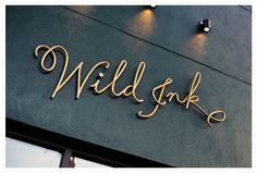 Cursive lettered store front sign in gold on charcoal colored wall