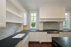 source: Oxford Development  Stunning open kitchen design with white Shaker style cabinetry and black center island. Carrara tiled backsplash with herringbone detail above stove top. Soapstone counters, traditional faucet and plate racks.