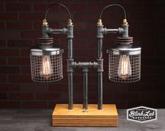 With a bit of steam-punk inspirations, this lamp is made of found items such as iron pipe fittings, brass wire fittings, toggle switch, wire bulb cages, and a layered wood base. The bottom of the wood base has felt attached to protect the furniture you place it on.  I try to make items that are off the beaten path. Apart from being a conversation piece, I want functionality, balance, and a mixture of materials and textures that make for an overall aesthetically pleasing design.  Vintage…