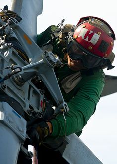 Aviation Structural Mechanic 3rd Class Makos Chhay performs a turnaround inspection on an MH-60R Sea Hawk helicopter from the Raptors of Helicopter Maritime Strike Squadron (HSM) 71.