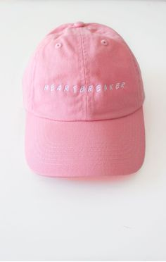 - Description Details: Six panel cap in pink with 'heartbreaker' embroidery & adjustable back with tri-glide buckle. Brand: NYCT Clothing. 100% Chino Twill. Imported. All accessories are final sale. S