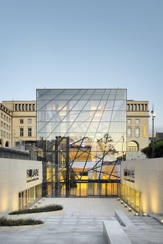 """An audacious architectural proposition to the city offers a newfound visibility to the former """"Palais des Congrès"""" by means of a poetic emblem embodied in the glass cube that forms the principal entry to SQUARE, Brussels Meeting Centre. Its tree"""