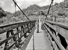 July 1940. Hazard, Kentucky. Miners' children crossing swinging bridge ...