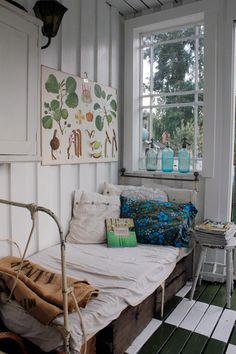 Summer sleeping porch with antique botanical print, blue glass seltzer bottles, crates, and painted wood ceiling, walls, and floor