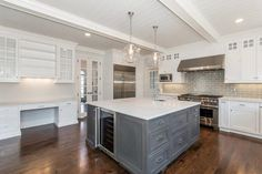 White and gray kitchen features planked ceiling with white wood beams accented with clear glass globe light pendants over square island painted gray topped with white marble framing small prep sink and glass-front wine fridge.