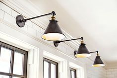 Metal library lights above the kitchen sink complement the black-painted windows. $169; Restoration Hardware