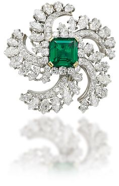 AN EMERALD AND DIAMOND BROOCH Of sunburst design, set with marquise-shaped and brilliant-cut diamonds, centering upon a cut-cornered square-cut emerald, 4.4 cm, with French assay marks for platinum and gold
