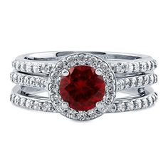This 3 piece halo ring set blends a passionate hue with a timeless style for a truly luxurious radiance. Made of rhodium plated fine 925 sterling silver. Features 1 carat round cut simulated ruby cubic zirconia (6.5mm) in 4-prong setting. Accented with 0.84 ct.tw round cut cubic zirconia in pave setting. Bands measure 6mm in width. Nickel free.