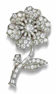 A diamond flower brooch, by Van Cleef & Arpels, circa 1950  The realistically modelled flower, with pavé-set brilliant-cut diamond leaves and petals, a brilliant and baguette-cut diamond stamen and a tapering baguette-cut diamond stem, diamonds approximately 6.55 carats total, signed Van Cleef & Arpels, numbered, French assay mark, later brooch fitting, fitted maker's case
