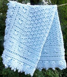 Listing is for a Pale Blue baby blanket made from a marle yarn ... white thread twisted around a blue yarn ... crocheted in a pretty shell pattern framed in squares of rosebuds. -- 36 x 27 Care is easy, just machine wash on gentle and tumble dry on low heat.  This item has been pre-washed using a dye-free / perfume-free detergent and was made and stored in a smoke free home.