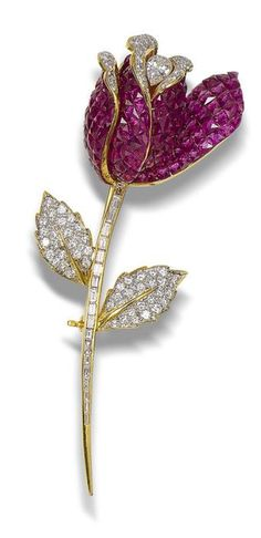 A ruby and diamond flower brooch  Realistically modelled as a rose, the petals of french-cut rubies within concealed settings and brilliant-cut diamonds, enclosing a pear-shaped diamond, the stem and leaves of brilliant and baguette-cut diamonds, pear-shaped diamond approximately 0.50 carat, remaining diamonds approximately 2.00 carats total, length 8.5cm