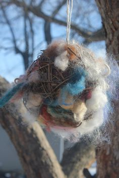 Nesting ball filled with various wools, silks and other fibers. Place in garden or near bird feeder for the birds to pull fibers to line their