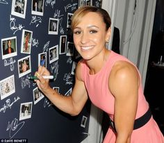 Getting used to fame: Jessica Ennis signs a wall at the party under a Polaroid photo of her