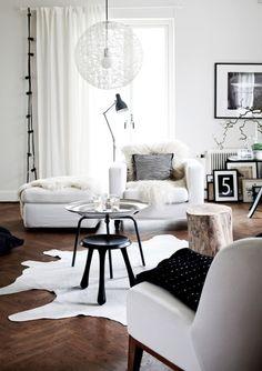Salon scandinave : mur et mobilier blanc, peaux de bêtes et fausses fourrures, présence du bois clair, décoration sobre (source : blog Deco-Design)