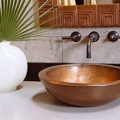 Classic Copper Sink A bronze wall-mount faucet pairs beautifully with a hand-hammered copper basin. Although this sink matches a hand-hammered copper tub (not shown), you needn't match your vessel sink to other fixtures in the room. Rather, create a focal point by choosing from porcelain, pottery, glass, or metal -- vessel sinks come in a wide range of materials, shapes, and sizes. TMI ..lol