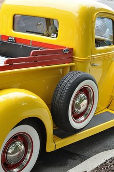 Yellow Ford, wide white walls, red rims, chrome hubcaps and trim rings