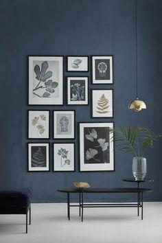 Zimmer in dunklem Grau mit einem Arrangement von zehn Bildern. Die Bilder zeigen Blätter und Pflanzen was dem Dekoelement ein Thema gibt, genauso wie die scheinbar ungeordnete Ordnung der aufgehängten Bilder - letztendlich folgen sie einer Linie. | Foto: Lilaliv