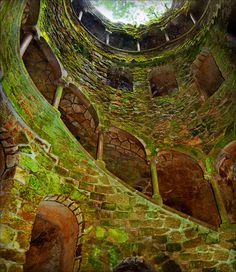 """Inside the initiation well -  Quinta da Regaleira  """"A subterranean tower"""" that sinks some 27 metres into the earth, made accessible by a monumental spiral stairway, full of esoteric and alchimical associations, makes the relation between Heaven and Earth intensely felt"""
