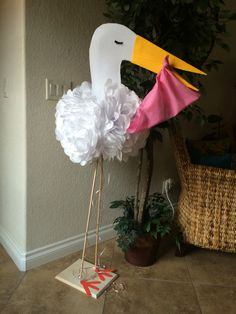 DIY Baby shower stork ! Use white tissue paper for feathers or body, felt for head and beak, 2 wood dowels, and pressed board for stand.