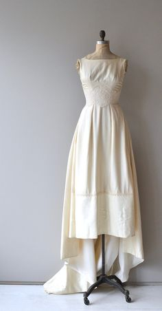 Vintage 1950s ivory raw silk wedding gown with wide set shoulders, scoop neckline, wide lace wrapped waist, slight bustle back with bow, detachable