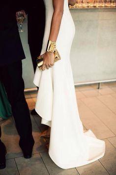 Vestido blanco con pulsera dorada, clutch y zapatos en el mismo tono.