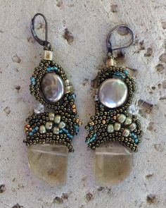 These elegant free form beaded earrings develop around a large German glass bead in a nice quarter angle shape. The glass bead is a soft olive green,