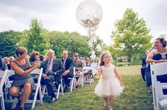 Flower Girl Walking Down the Aisle with Confetti Filled Balloon | Brides.com