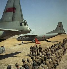 Soviet paratroopers peparing to embark on two An-12 transport aircrafts.