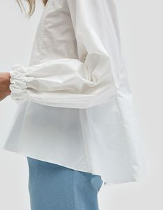 Feminine blouse from Fabiana Pigna in White. Round neckline. Concealed back zip closure. Long bishop sleeves with elasticated, recessed cuff. Contoured seams at bodice. Flared hem. • Shirting • 100% cotton • Dry clean • Made in USA