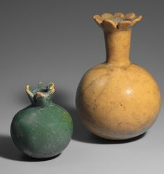 ca. 1295-1050 Egypt Pomegranate bottles, opaque glass. The small green unopened shape held the bitter juice used as an astringent. The yellow stylized open one held juice often mixed with wine. The pomegranate did not reach Egypt until the New Kingdom and then were planted for medicinal and other uses. They were also placed in burial chambers.