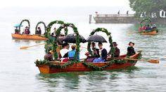 Geschmückte Fischerboote rudern bei Regen anlässlich der Fischerhochzeit in Tutzing über den Starnberger See in Bayern. Alle fünf Jahre wird in Tutzing an einen Wochenende die Hochzeit eines Fischers aus dem Jahr 1812 nachgespielt. | Bildquelle: dpa