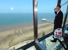 Room with a view: A visitor walks on the new glass walkway at the top of Blackpool Tower in Blackpool, north-west England. The new floor-to-ceiling glass observation platform will run along an entire side of The Blackpool Tower Eye.