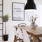 Zwarte hanglamp gecombineerd met houten tafel en witte stoelen. Extra pittig met ingelijste tekst in zwart op wit.