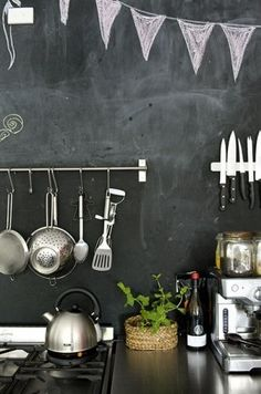 Blackboard behind cooker with pans hanging infront