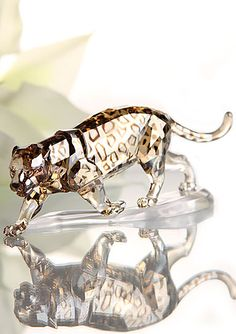 """Swarovski Rare Encounters Jaguar, Crystal Golden   $420.00 6 9/16""""  Item #1096796  With its elegant silhouette and powerful posture, the jaguar makes an impressive decoration object or ideal gift for men. This stunning sculpture gleams in Crystal Golden Shine with accents in Crystal Satin, reflecting the typical fur pattern of this dynamic wildcat. It stands on a matte clear crystal base."""