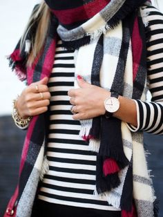 Loose cranberry plaid pattern blanket scarf paired with a thin striped long sleeve top.
