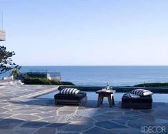 At Courteney Cox's Malibu retreat, the backyard infinity pool appears to continue directly into the ocean behind it. The Sutherland ottomans and Christian Liaigre table provide a perfect spot for the star to relax by the saltwater pool.