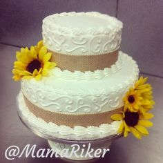 Two tier buttercream wedding cake. Burlap ribbon lined with pearls and simple buttercream scrolls. Silk sunflowers. Fall wedding :) love :) @Judy Riker